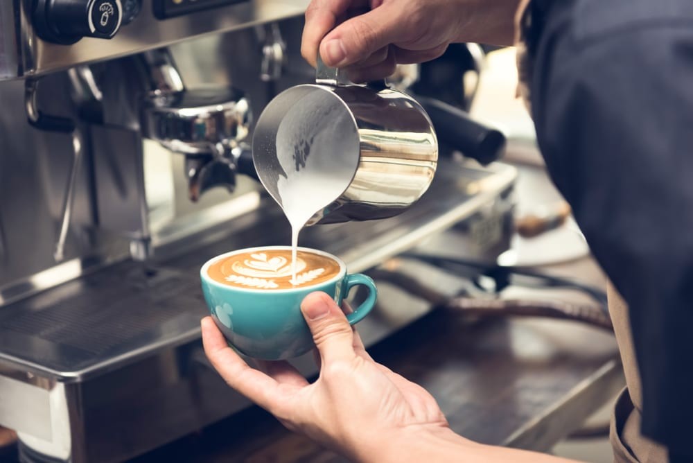 Professional barista pouring steamed milk into coffee cup